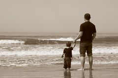 Father and son on the beach. They stand in the water and watch the sea royalty free stock photography
