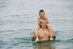 The father with the son on a beach. The father with the son have a fun in water stock photography