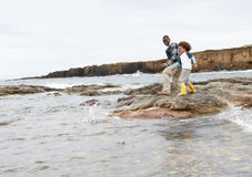 Father and son on beach. Playing stock image