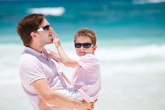 Father and son at beach. Portrait of young father and son at beach royalty free stock photography