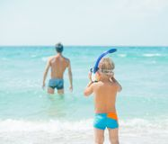 Father And Son At Beach. Cute little boy with snorkeling equipment on tropical beach, his father background Royalty Free Stock Images