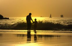 Father and son in the beach. Father and son at sunset in the beach Royalty Free Stock Photo