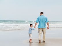 Father and son on the beach. Father and son holding hands and walking along beach toward the ocean Royalty Free Stock Image