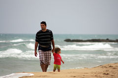 Father and son on beach royalty free stock images