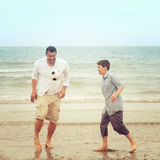 Father and son on the beach playing football. And have fun stock photo