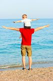 Father and son on the beach portray flight. Son sits on his fathers shoulders his arms to the side against the sea royalty free stock images