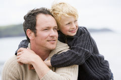 Father and son at beach smiling Royalty Free Stock Photos