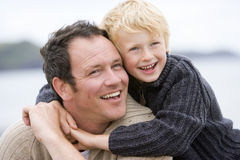 Father and son at beach smiling. Away from camera stock photos