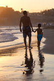Father and son on the beach at sunset Stock Photos