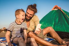 Father and son at the beach using phone. And having fun stock photography