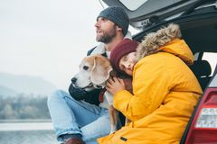 Father and son with beagle dog siting together in car trunk. Lat. E autumn time stock image