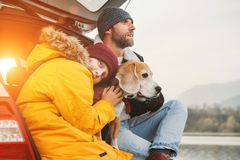 Father and son with beagle dog siting together in car trunk. Late autumn time stock photo