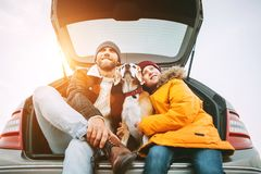 Father and son with beagle dog siting together in car trunk. Lon. Father and son dressed in yellow warm jacket with beagle dog siting together in car trunk. Long stock images