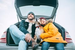 Father and son with beagle dog siting together in car trunk. Lon. G auto journey break royalty free stock photography