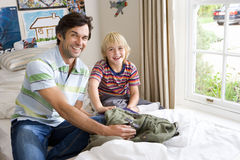 Father and son (6-8) in bedroom, smiling, portrait stock photo