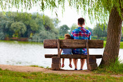 Father and son on the bench near the lake Stock Photos