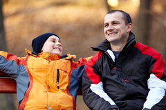 Father and son on a bench in park royalty free stock photography