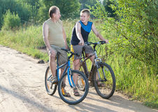 Two men by bicycles on the rural road in the summer sunny day Royalty Free Stock Image