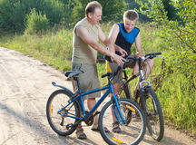The father and the son by bicycles on the rural road Stock Photography