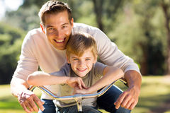 Father son bike. Portrait of happy young father and son on a bike Stock Images