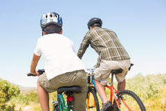 Father and son biking through mountains Royalty Free Stock Photography