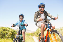 Father and son biking through mountains Royalty Free Stock Photo
