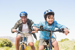 Father and son biking through mountains Stock Images