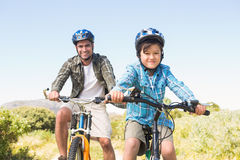 Father and son biking through mountains Stock Photo