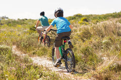 Father and son biking through mountains Stock Photos