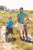 Father and son biking through mountains Royalty Free Stock Image
