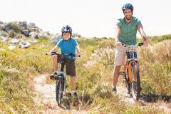 Father and son biking through mountains Royalty Free Stock Photos