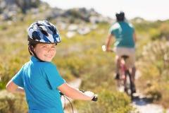 Father and son biking through mountains Royalty Free Stock Photo