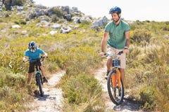 Father and son biking through mountains Stock Photos