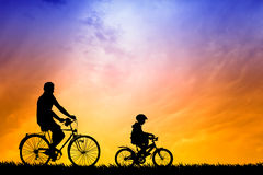 Father and son biking at sunset Royalty Free Stock Photos