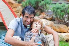 Father and son blowing bubbles Royalty Free Stock Image