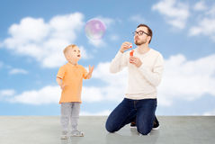 Father with son blowing bubbles and having fun Royalty Free Stock Photo