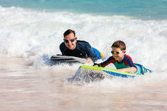 Father and son boogie boarding. Father and son surfing on boogie boards royalty free stock image