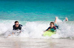 Father and son boogie boarding. Father and son surfing on boogie boards stock photo