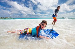 Father and son boogie boarding. Father and son surfing on boogie boards royalty free stock images