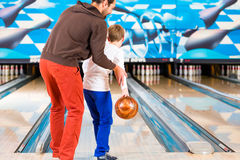 Father and son in bowling center Stock Photo