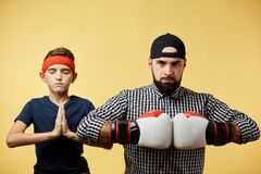 Father and son with boxing gloves doing namaste gesture on yellow