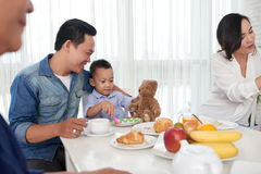 Father and Son at Breakfast with Family Royalty Free Stock Image