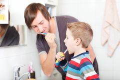 Father and son brushing teeth Stock Photos