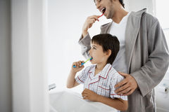 Father And Son Brushing Teeth Royalty Free Stock Photos