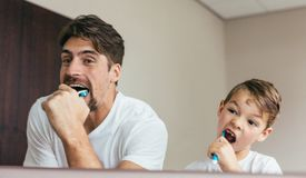 Father and son brushing teeth in bathroom. Young men with his son together brushing teeth and looking in mirror Stock Photo