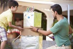 Father And Son Building Model Robot In Garden Stock Photos