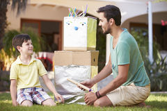 Father And Son Building Model Robot In Garden Royalty Free Stock Photos