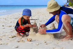 Father and son building sand castle on the beach Stock Photo