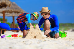 Father and son building sand castle on tropical Royalty Free Stock Photography
