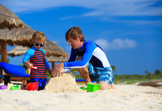 Father and son building sand castle on tropical Royalty Free Stock Photo
